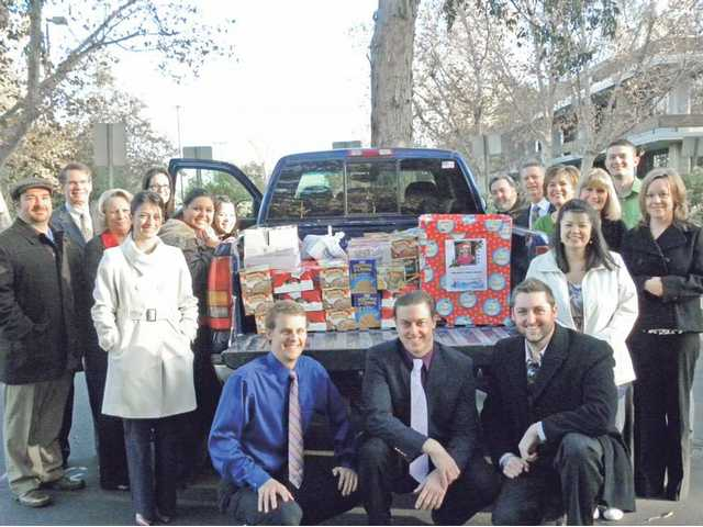 Employees of Petersen International Underwriters in Valencia pose with the truckload of food collected and donated to the Santa Clarita Valley Food Pantry this year.