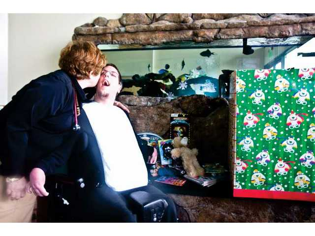 Daniel Mills (right) gets a kiss from Rochelle Freedman, medical director at Prima Pediatrics in Canyon Country and a family friend of Mills for 16 years. Mills, who has cerebral palsy, donated $440 he raised for his birthday to buy Christmas gifts for less fortunate children.