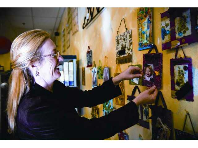 "Rhonda Coleman, co-owner of Rooms & Blooms in Valencia, places a gold butterfly on one of the ""Instant Attraction"" magnet boards she sells."