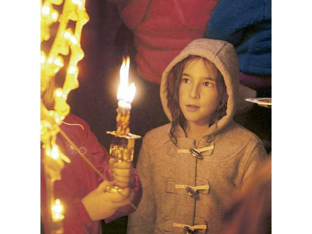 Dina Blazer, 10, participates in the Hanukkah Menorah lighting ceremony in Stevenson Ranch on Saturday.