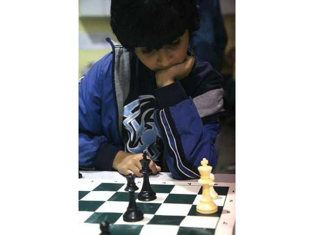 Ten-year-old Akshay Trisal thinks about his next move during the chess-a-thon fundraiser Saturday at the Lighthouse Learning Center. The event raised funds to provide new chess sets, lesson books, clocks, pencils, stickers, carrying cases and more for CYCL students.