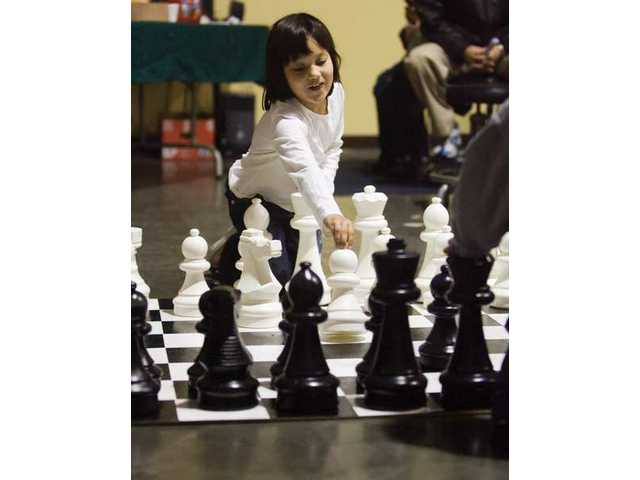Five-year-old Nadia Naciejewski plays with the giant chess game during the chess-a-thon event at the Lighthouse Learning Center Saturday.