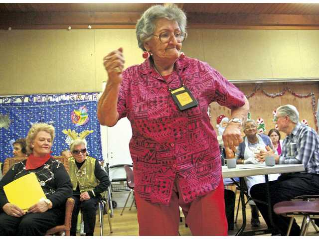 Orona Conzuelo dances to holiday music as the Senior Choir and Orchestra group performs at the Santa Clarita Valley Senior Center on Monday.