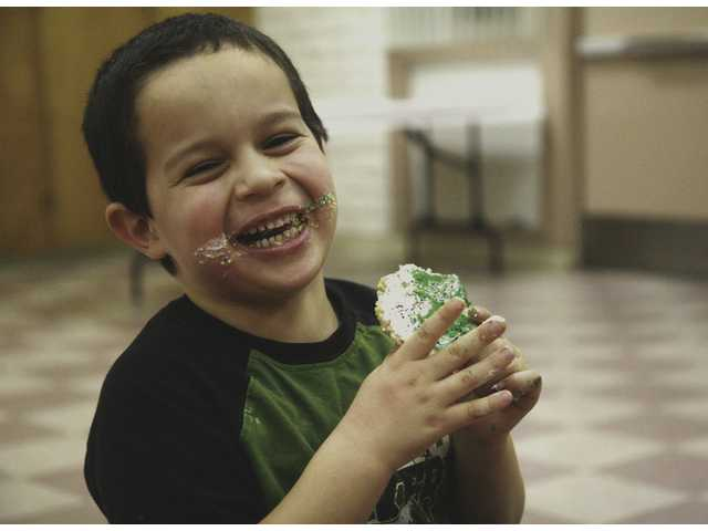 Eyan Document, 5, enjoys a cookie he decorated during Kids' Night Out Friday at the Santa Clarita Park community room .