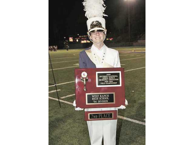 Assistant Drum Major Emily Brown shows off the award given to West Ranch High School Marching Band and Color Guard.