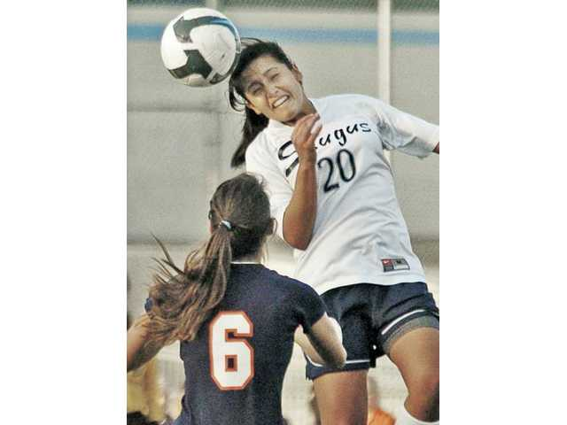 Saugus' Ysabelle Padron (20) goes up for a header over Chaminade's Ana Alvarado Tuesday at Saugus High.