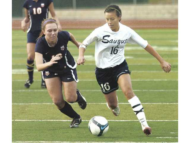 Saugus' Emily Relles (16) dribbles downfield as a Chaminade player gives chase Tuesday at Saugus High School.