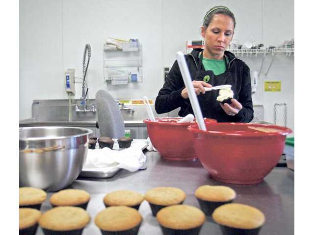 Genine Baldree prepares a batch of cupcakes for her store. All of her cupcakes, with the exception of German chocolate, are also offered gluten-free.