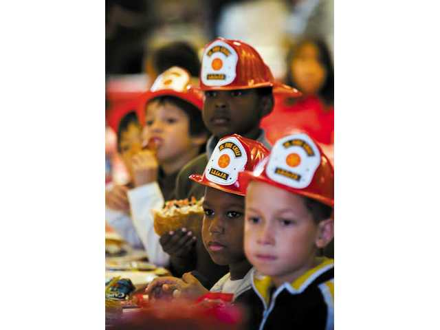 "Children from around the valley were given fireman's helmets from the L.A. County Fire Dept. Station 149 during the Southland Regional Association of Realtors ""Sparks of Love"" holiday luncheon for 80 to 100 at-risk children, held at the Castaic Sports Complex."