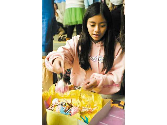 Sixth-grader Kim Tsuda made paper lanterns using eggshell and origami figures to sell as part of Castaic Middle School's math marketplace.