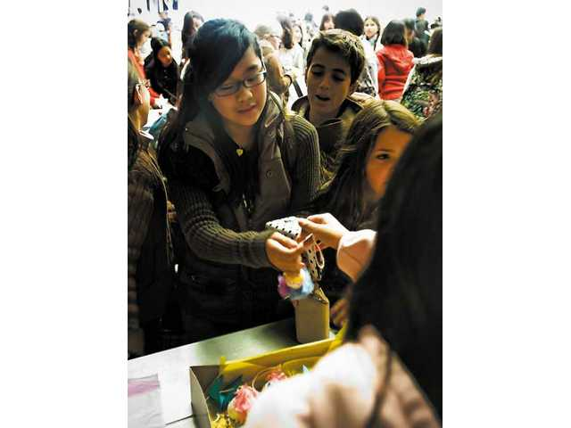 Muriel Valencia buys one of Kim Tsuda's paper lanterns at Castaic Middle School's math marketplace  Tuesday.