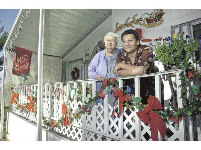 Polynesian Mobile Home Park residents Judy Baker, left, and her son Larry Rodriguez pose on the porch of their mobile home in Newhall on Wednesday. The residents may have to move if a space rental increase goes through to offset the cost of flood damage repairs at the park.