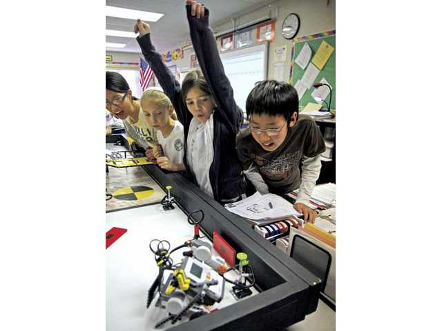 Left to right, members of the Robo Huskies team Jihee Han, Carly Magalski, Kailey Bevan and Jonghak Won of the Pico Canyon Elementary School robotics program react as their robot successfully finishes the course during a practice run on Wednesday afternoon.