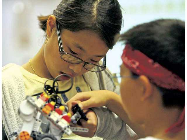Jihee Han, left, and Luke Kim assemble the final touches on the Robo Huskies' robot during their after-school meeting on Wednesday.