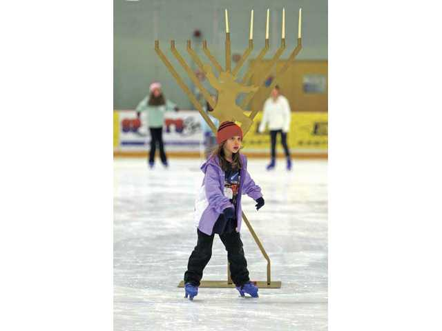 Melissa Griffin, 8, skates around a menorah during the fourth day of Hanukkah celebration at the Valencia Ice Station on Monday evening. Members of Chabad of SCV skated around the rink and later said two Hannukah blessings as they lit the candles.
