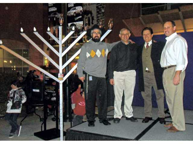 Chabad of SCV's Rabbi Choni Marozov, left, Rabbi Howard Siegel of Congregation Beth Shalom, Or Emet's Rabbi Jay Levy and Temple Beth Ami's Rabbi Mark Blazer, pose near a lit menorah at Westfield Valencia Town Center. SCV's four congregations came together Sunday for a Hanukkah Family Festival on the third night of Hanukkah.