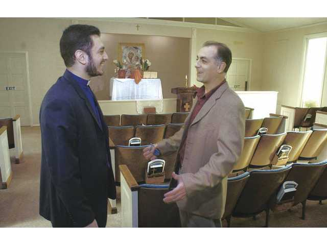 Parish Council Treasurer Harry Soghomonian, right, welcomes Father Nerses Hayrapetyan as he visits the new Armenian Apostolic Church of Santa Clarita in Newhall on Thursday.