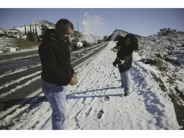 Tony Belfiore and his wife Wivina, both of Agua Dulce, play in the snow while stuck in traffic on Sierra Highway Thursday morning. They moved here from Northern California four years ago, and she said this is the first time they've had snow so close to home.
