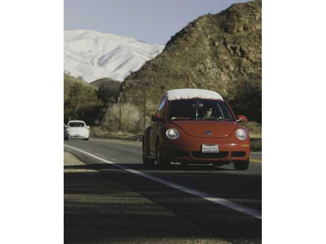 The driver of a snow-laden Volkswagen Beetle makes his way south on Sierra Highway Thursday.