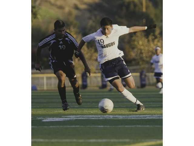 Centurion Erick Esquivel (19) battles with Triton Edgar Suarez (19) Thursday at Saugus.
