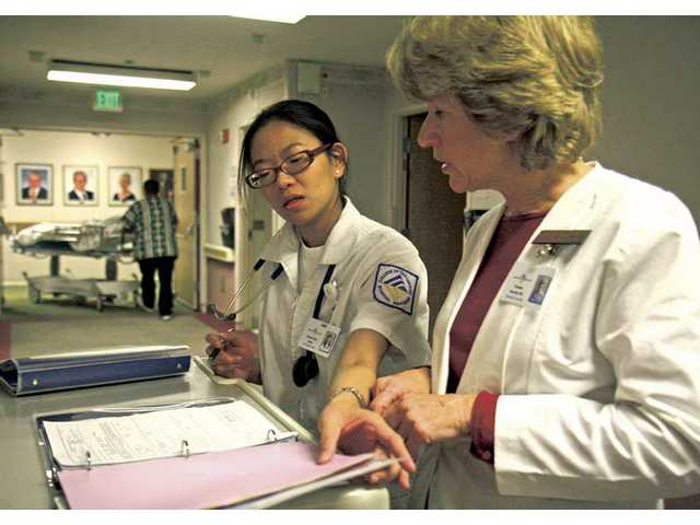 College of the Canyons Resident Nursing student Joanne Kelly Javier and nursing professor Pamela Borrelli look over a patient's chart in Henry Mayo Newhall Memorial Hospital Tuesday morning.