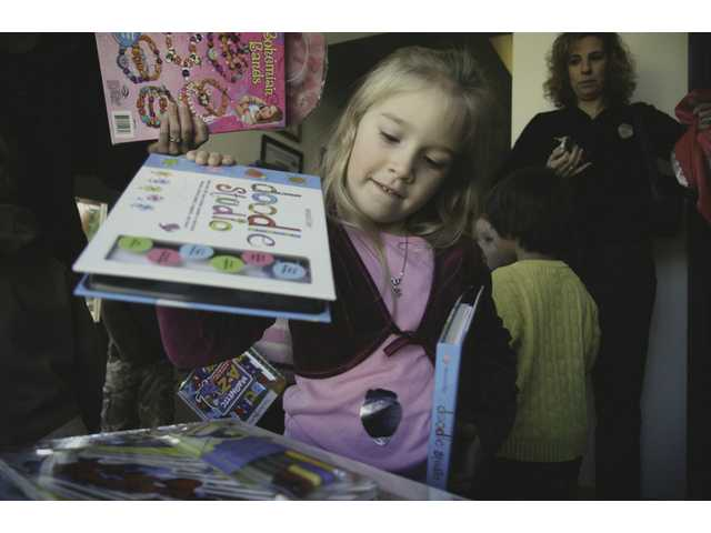 Alyssa Azani, 4, drops off donated toys for the Toys for Tots drive at Fire Station 124 Friday morning. The group of preschoolers from Temple Beth Ami also took a tour of the station.