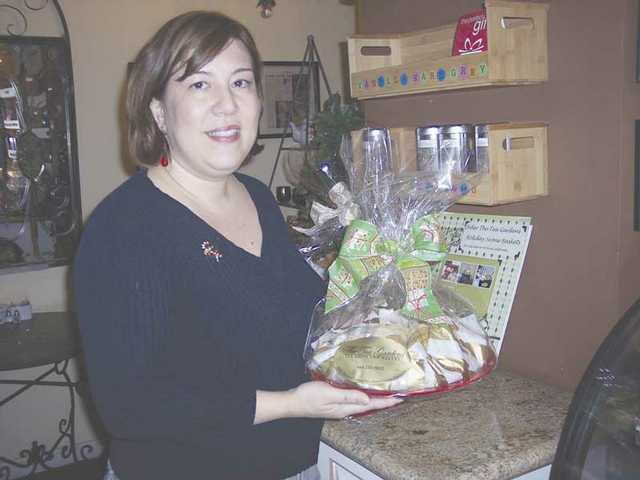 Tea Gardens owner Elda Meguerditchian displays a festive plate of fresh baked scones and other dessert goodies that pair perfectly with a tasty cup of tea.