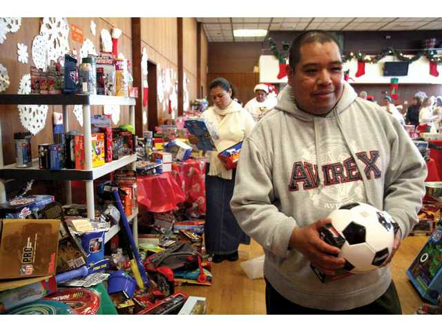 Arturo Chacon, from Canyon Country, picks out a soccer ball as a Christmas present for his son during the Santa Clarita Sheriff Station's toy drive Saturday at College of the Canyons. The event, which took place from 8 a.m. to 5 p.m., allowed more than 500 pre-registered families to pick out gifts for their children.