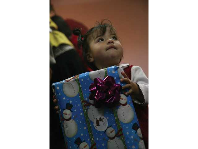 One-year-old Kenia Ortiz, of Newhall, receives a gift from Toys for Tots at Victory Tabernacle Church Sunday.