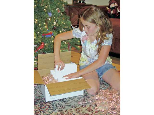 Rosedell Elementary School student Emily Hood, 11, stuffs holiday cards with candy canes in a box to be shipped to one of many U.S. platoons worldwide. Emily, with the help of students on campus, made 3,000 cards this year.