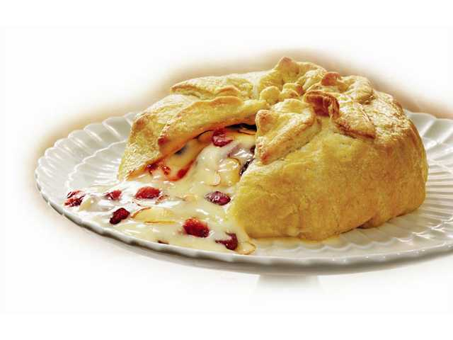 Holiday Brie en CrouteThaw: 40 minutes / Prep: 15 minutesBake: 20 minutes / Stand: 45 minutesMakes: 12 servings1 egg1 tablespoon water1/2 of a 17.3-ounce package Pepperidge Farm Puff Pastry Sheets (1 sheet), thawed1/2 cup apricot preserves or seedless raspberry jam1/3 cup dried cranberries1/4 cup toasted sliced almonds1 (13- to 16-ounce) Brie cheese round1 package (13 ounces) Pepperidge Farm Entertaining Quartet Distinctive Crackers 1. Heat the oven to 400°F. Beat the egg and water in a small bowl with a fork. 2. Unfold the pastry sheet on a lightly floured surface. Roll the pastry sheet into a 14-inch square. Spread the preserves on the pastry to within 2 inches of the edge. Sprinkle with the cranberries and almonds. Place the cheese in the center of the pastry. Fold the pastry up over the cheese to cover. Trim the excess pastry and press to seal. Brush the seam with the egg mixture. Place seam-side down onto a baking sheet. Decorate with the pastry scraps, if desired. Brush with the egg mixture. 3. Bake for 20 minutes or until the pastry is golden brown. Let stand for 45 minutes. Serve with the crackers.