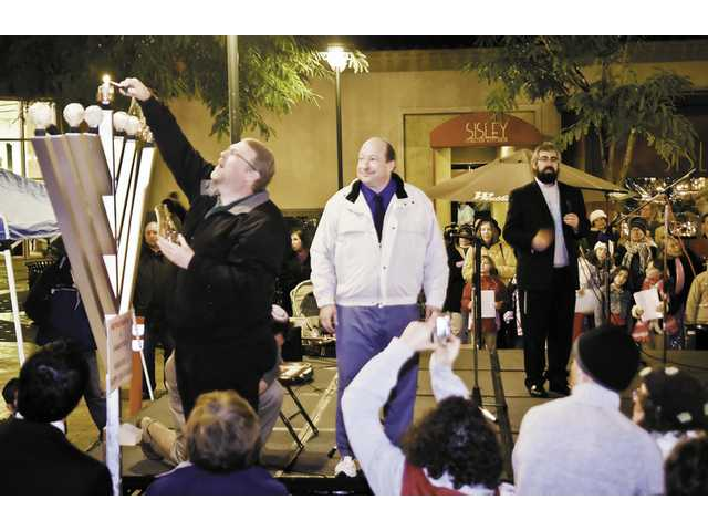 Santa Clarita's new mayor, Frank Ferry, lights the menorah at the Westfield Valencia Town Center Monday night. The Chanukah event included singing, food and blinking balloons for the kids.