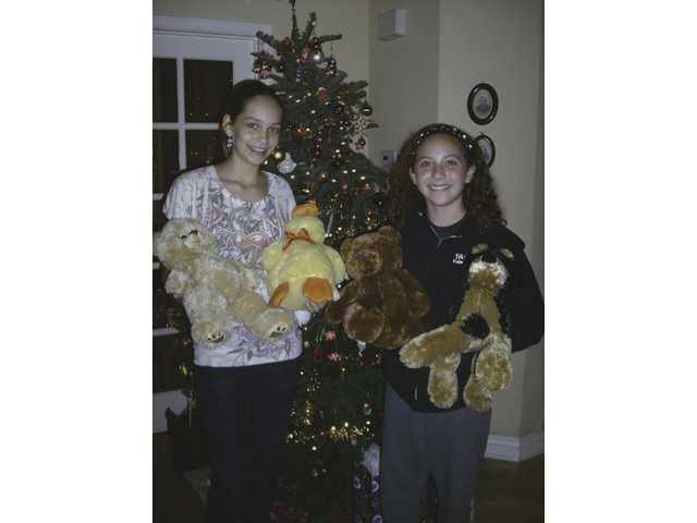 Alison Jordan, right, and her friend, Emma Boon, collected more than 50 stuffed animals to give to needy children for holiday gifts.