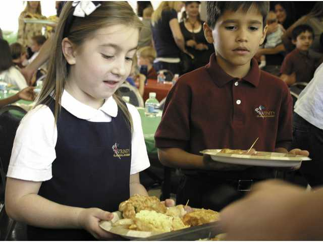 Hope Peacock and Gregory Salazar sample some of the delectable offerings at Trinity Classical Academy's first grade Heritage Festival.