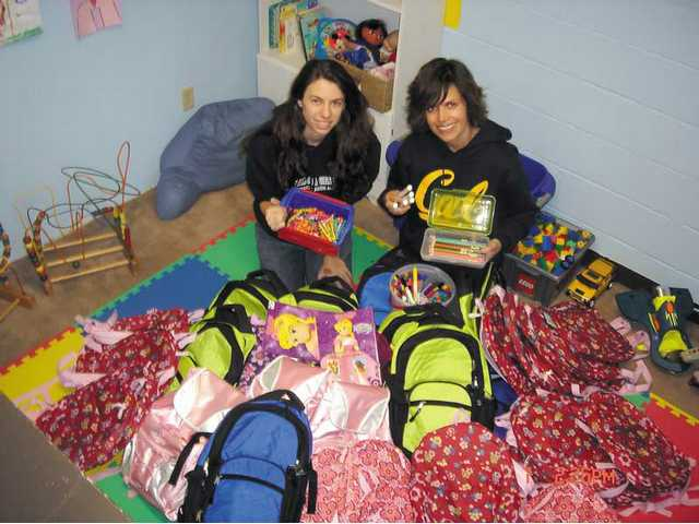 Jeriann Lynds, left, with Almira Agosto, director of Prevention Services for the SCV Domestic Violence Center, displays some of the backpacks Lynds assembled for local students.