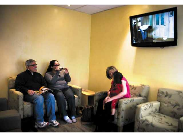 Larry Velez, far left, watches as his granddaughter Natalie Petrillo, far right, is videotaped by his daughter Allie Velez, left, as she's bounced on grandmother Lorrie Velez's knee. Seven-pound 11-ounce Sophie Marie Petrillo was born Tuesday morning. Her family was the first to use the new waiting room at the labor maternity ward at the Henry Mayo Newhall Memorial Hospital.
