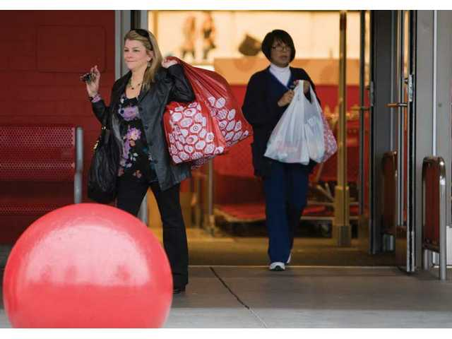 Left: Pam Campbell of Valencia leaves Target with bags of wrapping paper Wednesday morning.