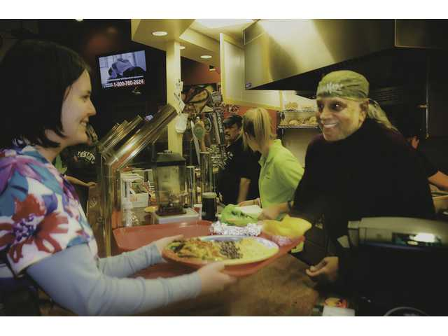 Abby Savell (left) is handed her fajitas by Rama Iyengar, the owner of Una Mas, at the Golden Valley shopping center during their grand opening held Dec. 11.