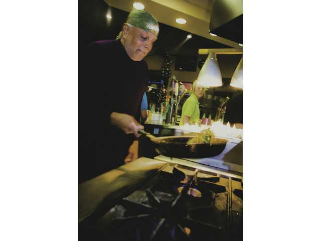 Rama Iyengar makes fajitas during the Dec. 11 grand opening of Una Mas on Golden Valley Road.