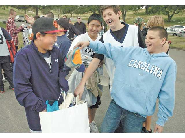 Players of the Playmakers Basketball Association laugh as Justin Coleman, 12, pulls a hat from the bag Keston Hiura, 13, is holding. The group donated hundreds of hats and caps to cancer victims through the Sharing Hope Through Hats program at Eternal Valley Memorial Park Mortuary on Dec. 26.