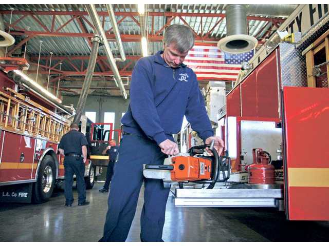Fireman Rich Hall makes sure a chain saw works properly during a routine check on Friday.