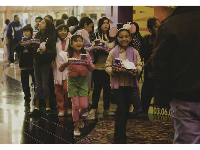Fifth-grade students at McGrath Elementary School walk toward the theater at Edwards Cinema in the Valencia Town Center.