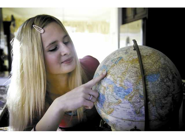 Foreign exchange student Kristina Micunekova points out her home country of Slovakia at her host home in Valencia.