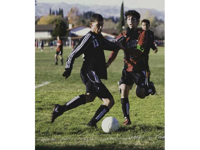 Hart captain Armand Simian (18) goes up against an unidentified Palmdale player (13) Friday in the first day of the Hart Showcase Tournament. The Indians split their two games of the day, losing their first 2-1 to Paraclete High of Lancaster and winning their second 1-0 over Palmdale.