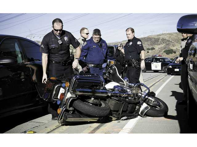 Two Los Angeles Police Department officers and two California Highway Patrol officers look at the motorcycle belonging to LAPD officer Sheldon Williams, who collided with multiple vehicles on his way to work.