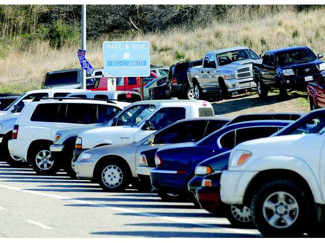 Cars are parked on the side of the road at the park-and-ride lot at San Fernando Road and the 14 freeway Tuesday.