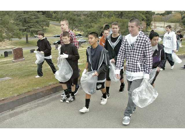 Players of the Playmakers Basketball Association fan out with gloves and plastic bags to pick up trash at Eternal Valley Memorial Park and Mortuary in Newhall on Saturday.