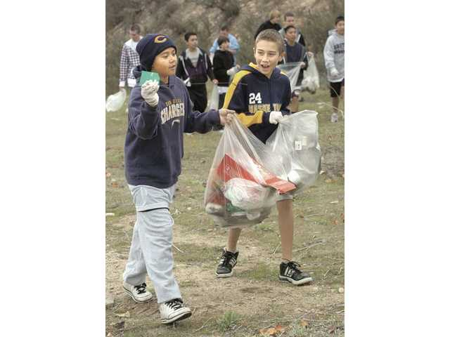 Will Picketts, 11, left, and Alex Morales, 11, fill their bags with trash.
