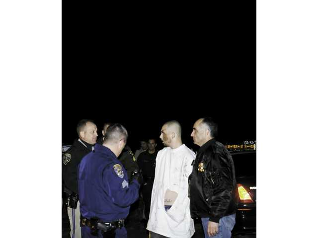 Los Angeles Sheriff's Department and California Highway Patrol personnel take Ryan Ogden into custody for felony evasion after he attempted to escape in a stolen car Saturday.