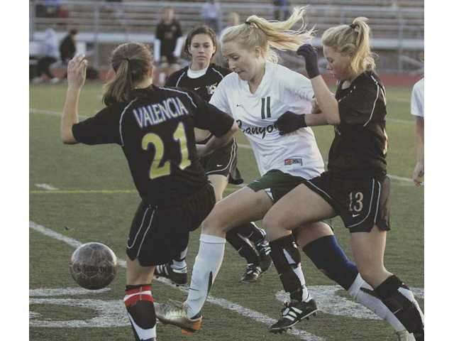 Canyon's Katherine Hanson (11) fights for the ball with Valencia's Haleigh O'Connell (13) and Alyssa Morse (21) Tuesday at Canyon High.